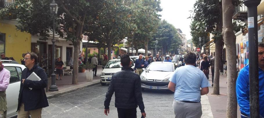 gruppi di turisti tra auto e scooter