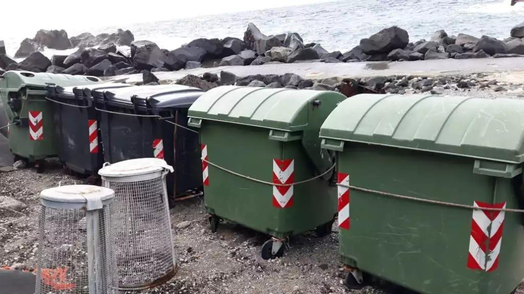 I cassonetti legati con catene per evitare che finiscano in mare